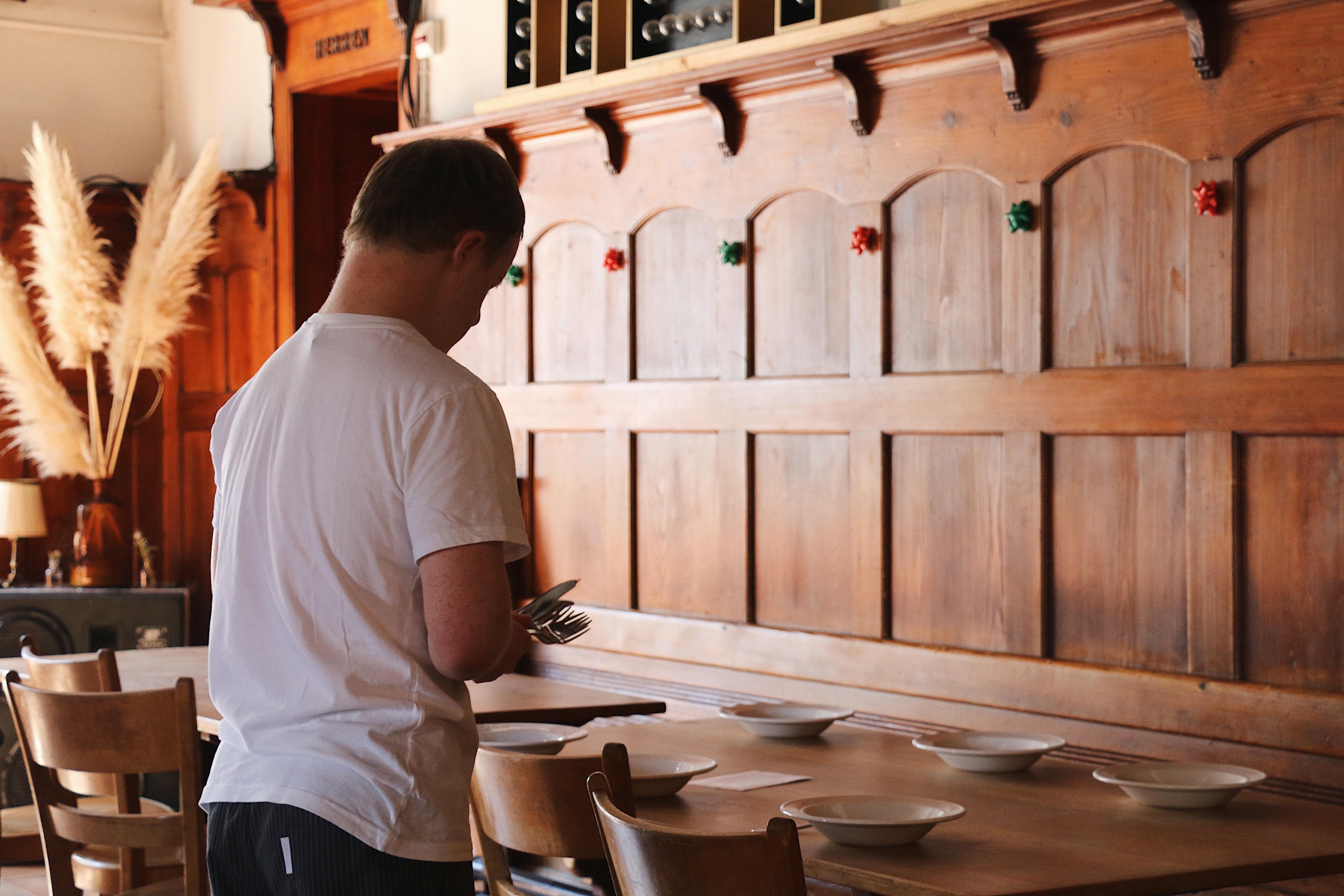 Ein Mitarbeiter im weissen Hemd und schwarzer Hose deckt einen Tisch. Er legt besteck neben weisse Teller, die auf einem Holztisch stehen. Auch die Einrichtung ist von einer Holzwand geprägt, die im Hintergrund zu sehen ist.