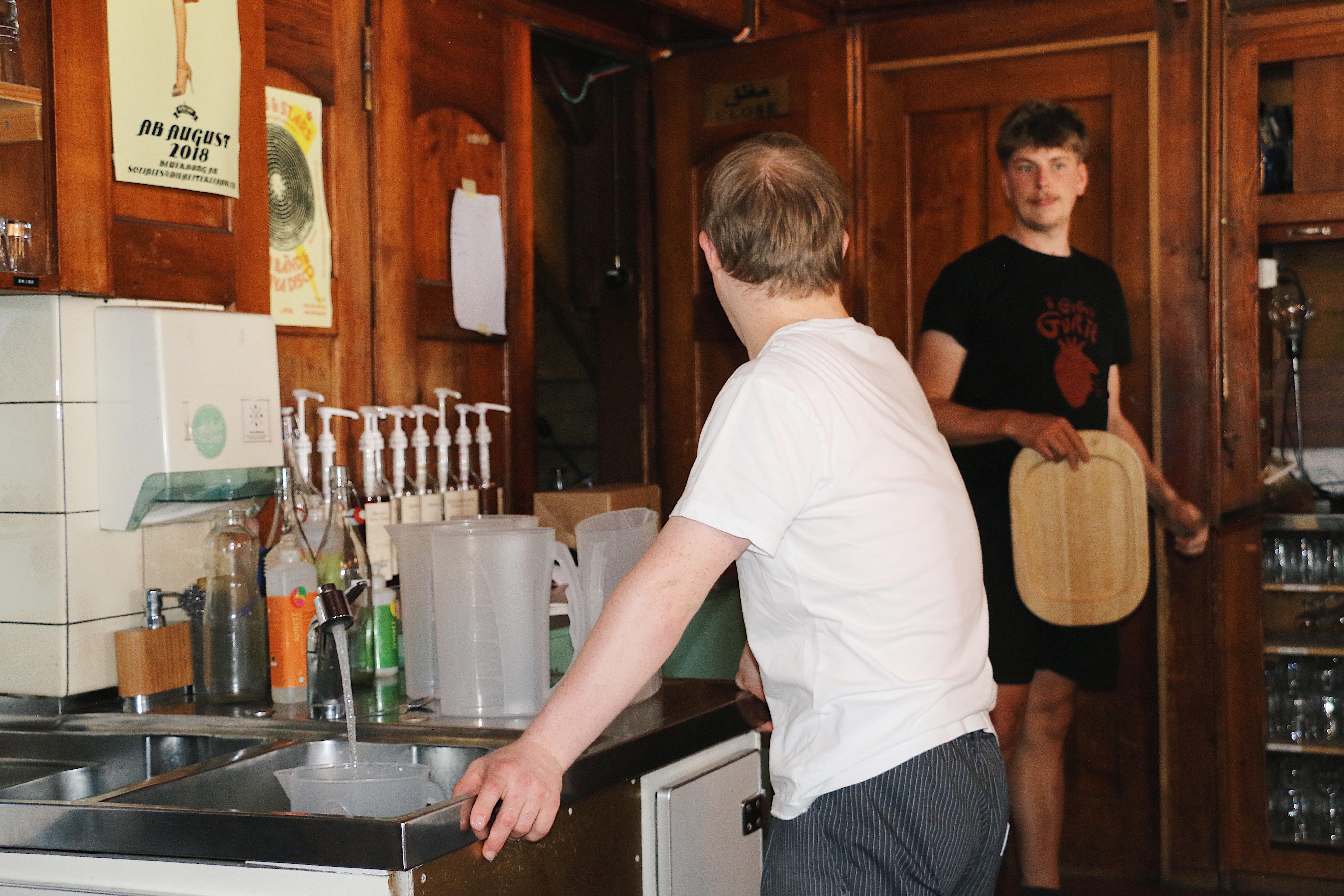 Ein Mitarbeiter füllt an einer Spüle Leitungswasser in einen Behälter. Er hat seine Hände auf die Arbeitsfläche abgestützt und wirkt entspannt. Er schaut zu einem anderen Mitarbeiter, der ein Tablett in der Hand hält und gerade den Raum betritt.