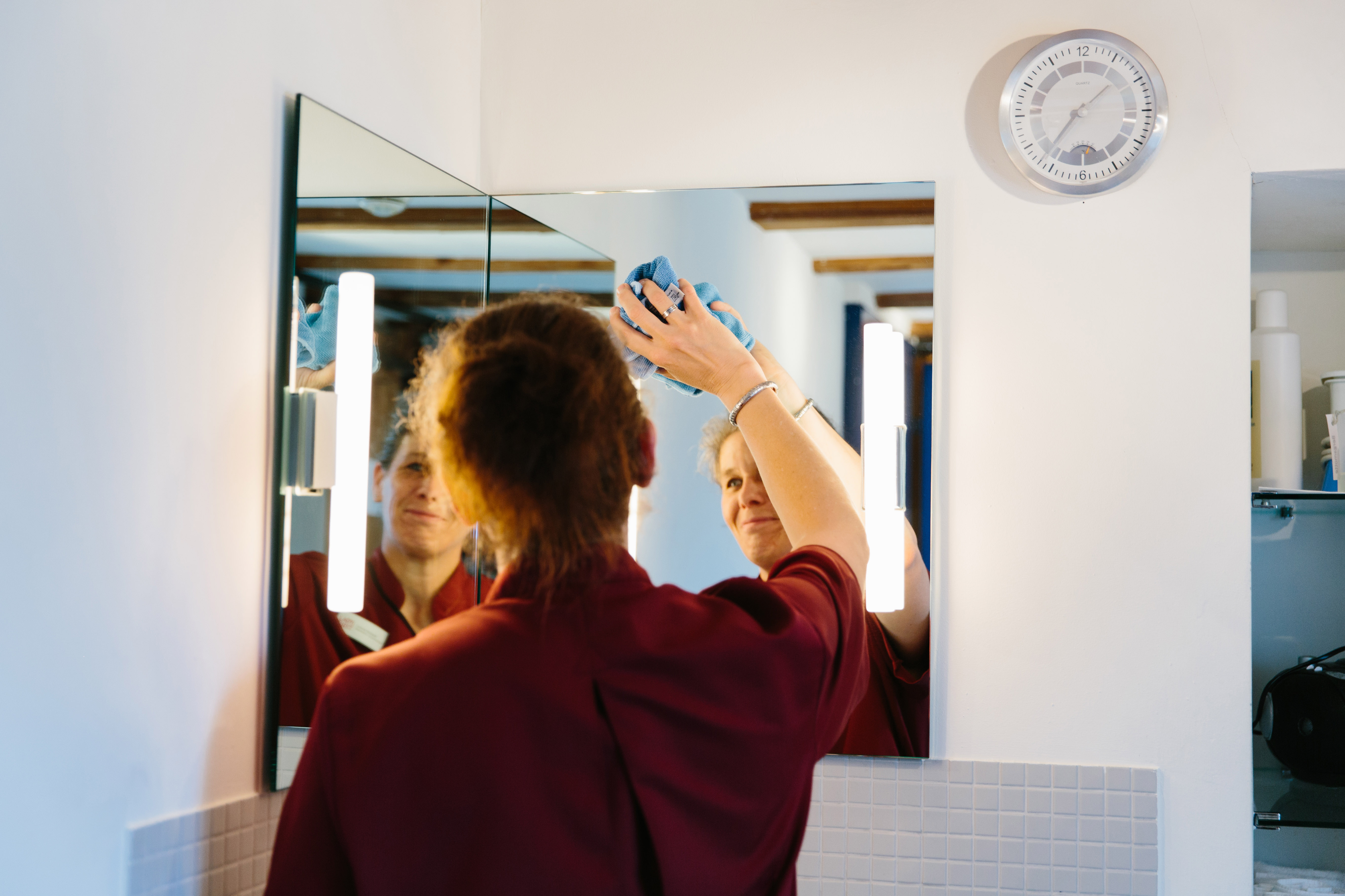 Eine Mitarbeiterin reinigt mit einem Tuch einen Spiegel. Sie trägt rote Arbeitskleidung. Ihr lächelndes Gesicht spiegelt sich doppelt im Spiegel, der an einer Ecke des Raumes installiert ist.
