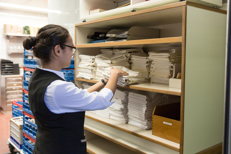 Eine Mitarbeiterin legt gefaltete Wäsche in einen offenen Schrank. Im Hintergrund sind verschiedene Kisten zu sehen. Das Bild vermittelt einen Eindruck von Ordnung und Sauberkeit.