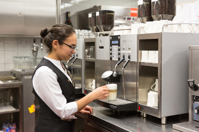 Eine Servicemitarbeiterin mit schwarz-weisser Arbeitskleidung, Brille und zusammengebundenen Haaren, bereitet an einer grossen Kaffeemaschine ein Kaffeegetränk vor.